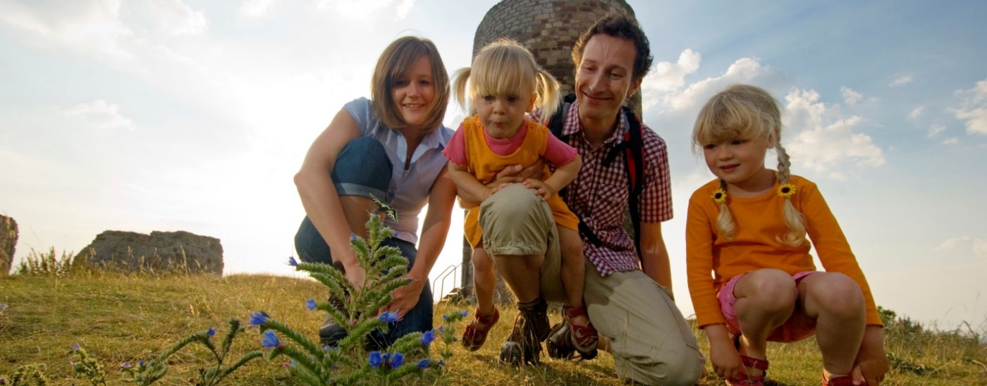 Eltern und kleiene Tochter in der Sonne auf einer Wandertour
